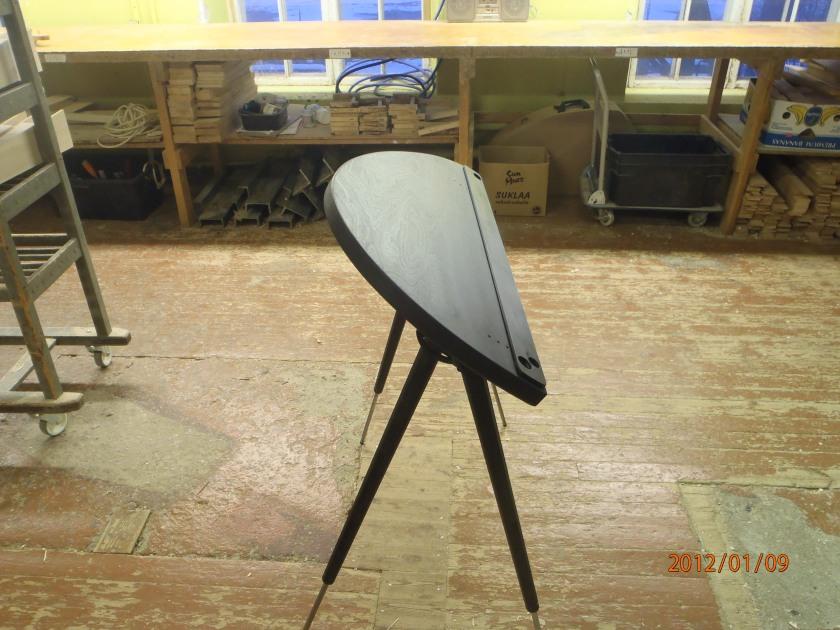 Seisten soittoon tarkoitettu. joka suuntaan säätyvä soittopöytä. Tässä mustana.